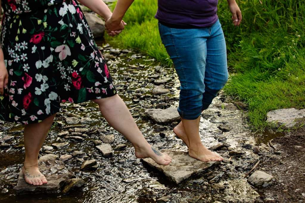 Couple holding hands and rolled up jeans in creek