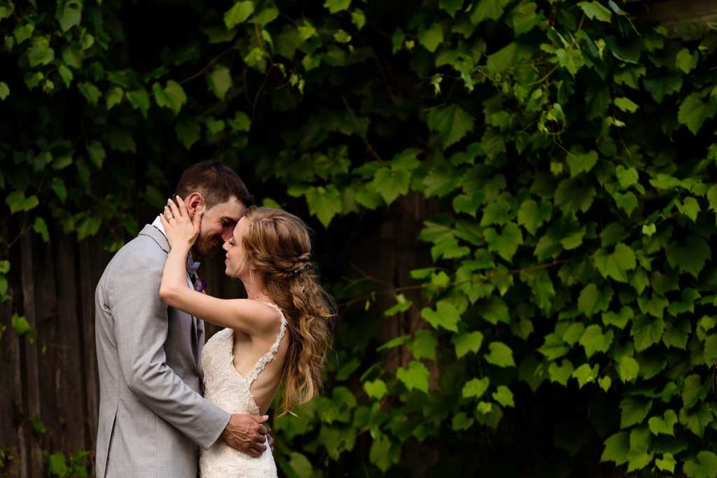 Bride and groom kissing in patch of lush greenery at Strathmere wedding