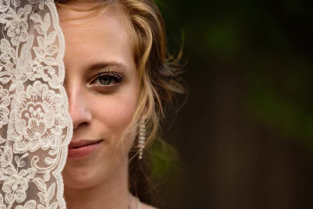 Interesting photo of bride with lace veil partially covering her face