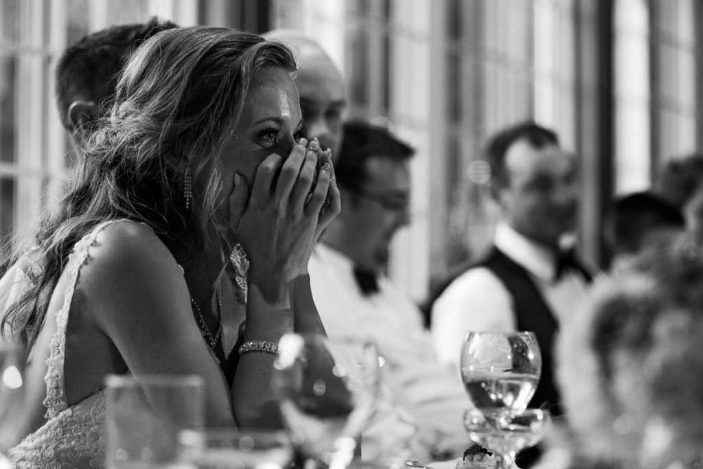 Bride at head table laughing during speeches at intimate Strathmere wedding