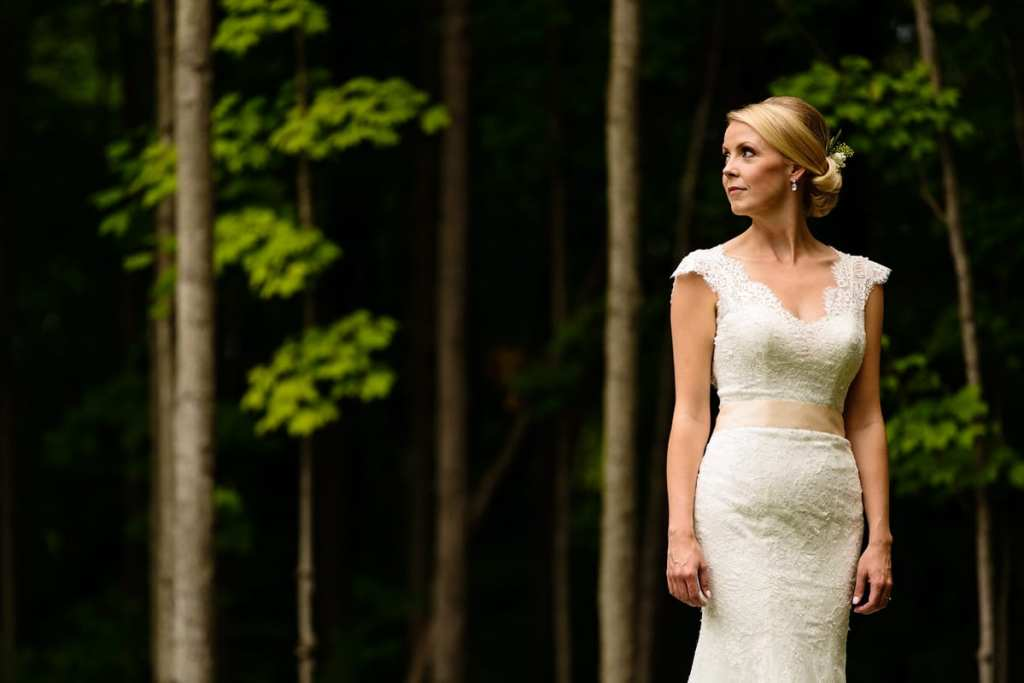 stunning bride in all lace gown against forested background