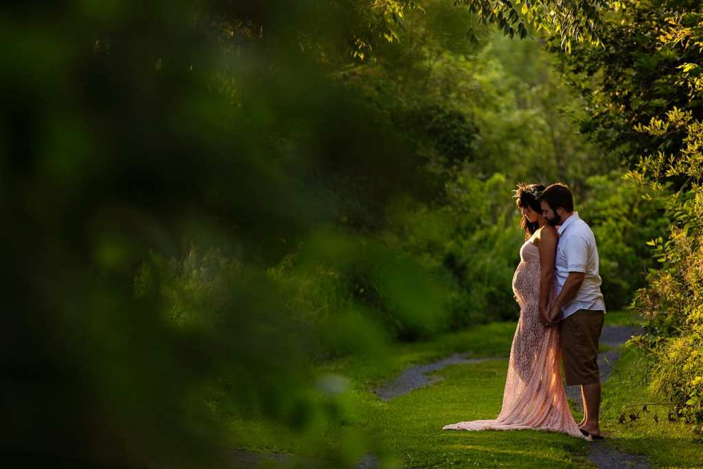Bohemian pregnant woman on nature trail with husband standing behind her
