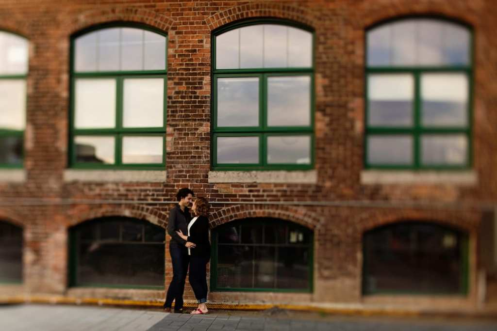 Couple kissing in front of modern industrial loft in urban engagement session