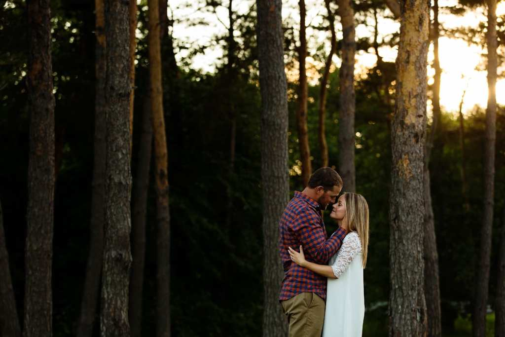 Woman in white dress and fiance in sunset forest engagement shoot