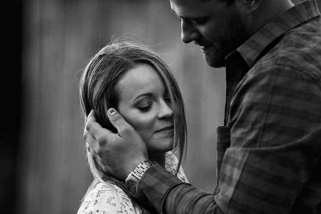 Rugged man holding fiancee's hair back from face
