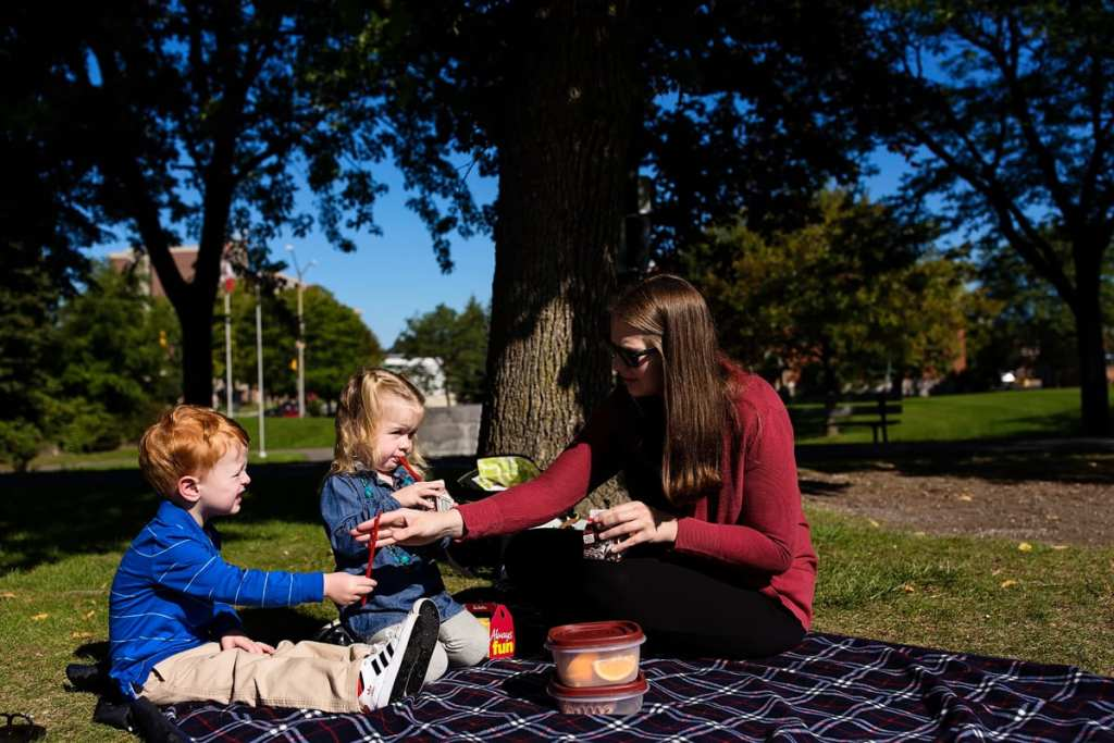 mom with kids having sunny summer picnic in Cornwall park family session