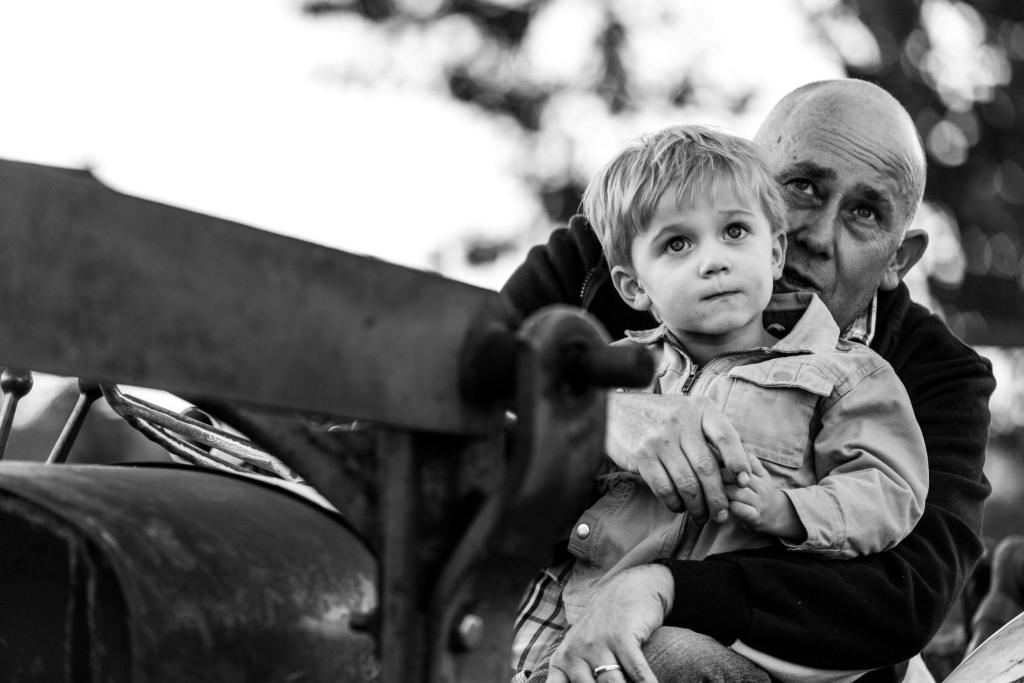 little blonde boy and dad sitting on tractor in rural family shoot