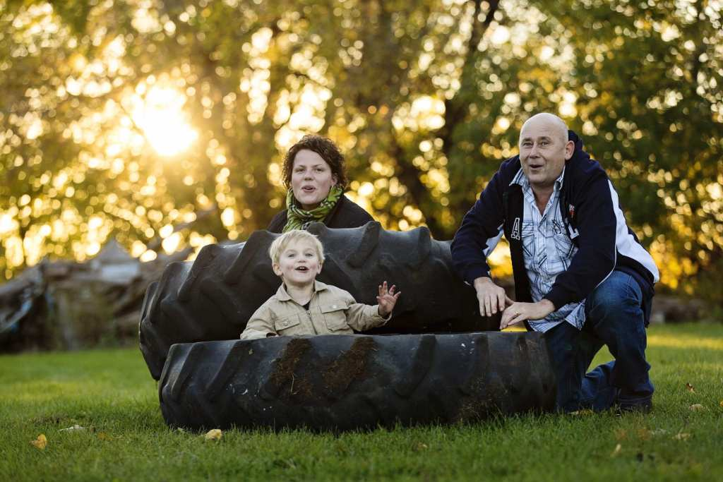 mom and dad playing in tractor tires with young blonde boy rural family shoot