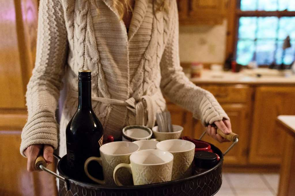 young woman in cozy cable knit sweater serving coffee and baileys with mugs on serving tray