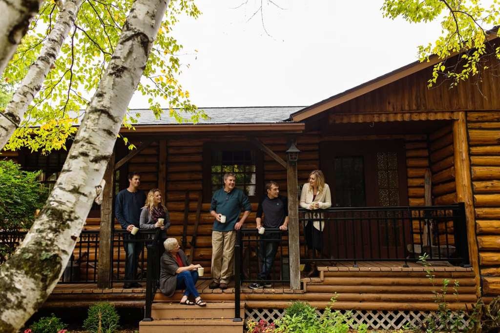 family sharing coffee and time on deck of log cabin during Ontario Casual Family Portraits
