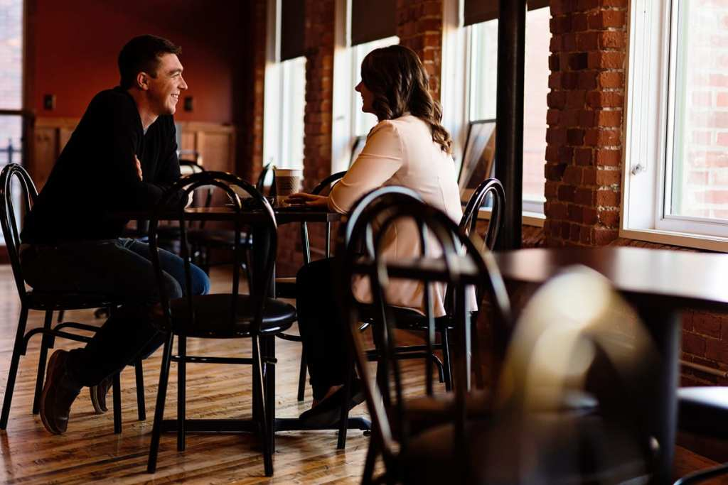 couple in sunlit coffee shop in fall Cornwall engagement session