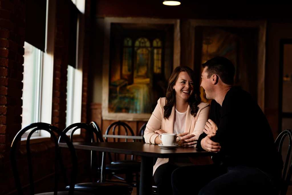 couple laughing and smiling in coffee shop during Cornwall engagement session