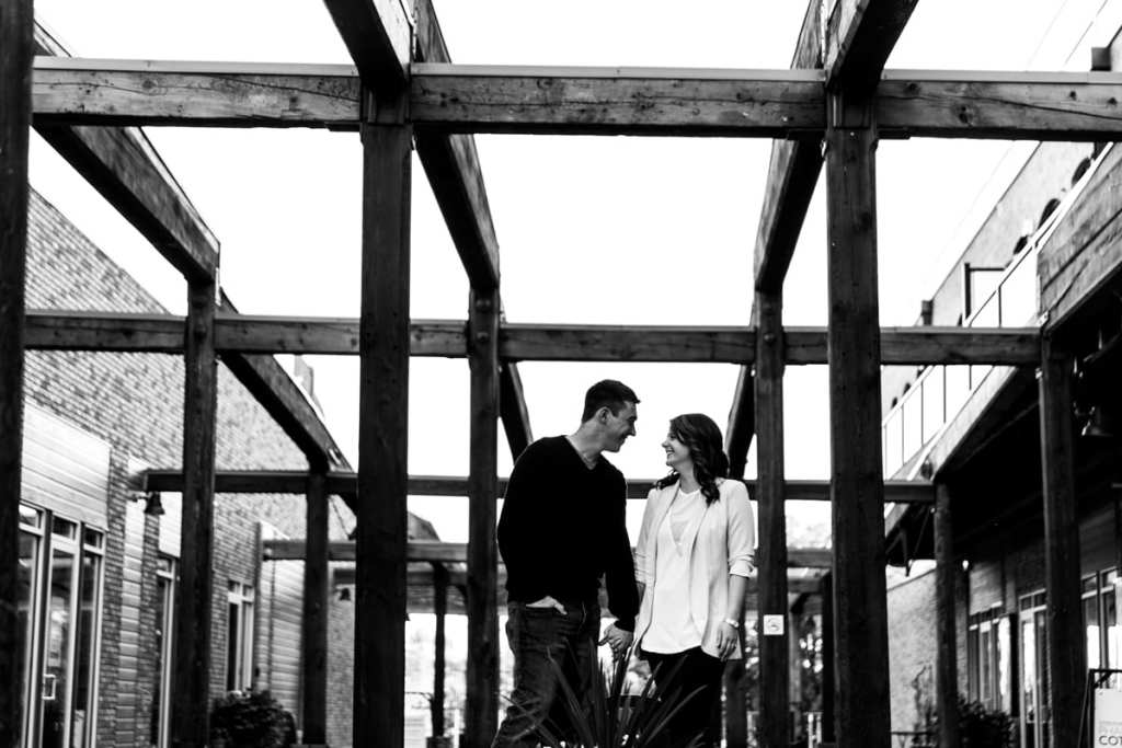 couple holding hands under outdoor patio with large rustic beams