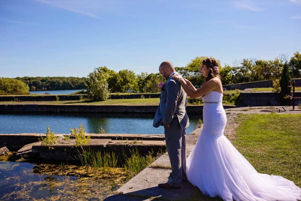 bride puts hands on groom's back during first look