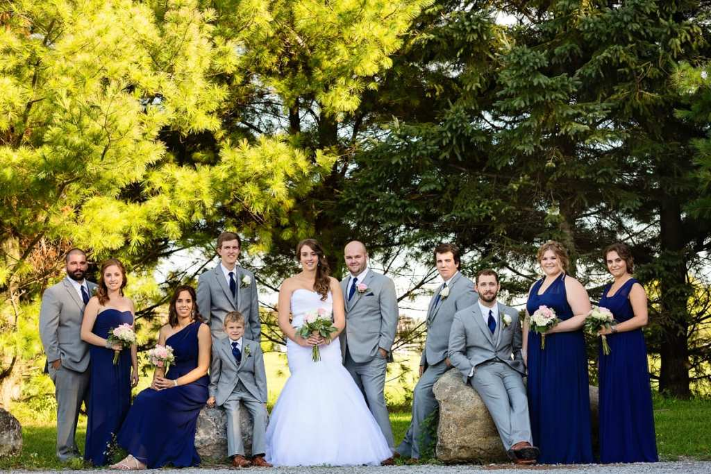 Cornwall wedding party standing around rocks in front of pines