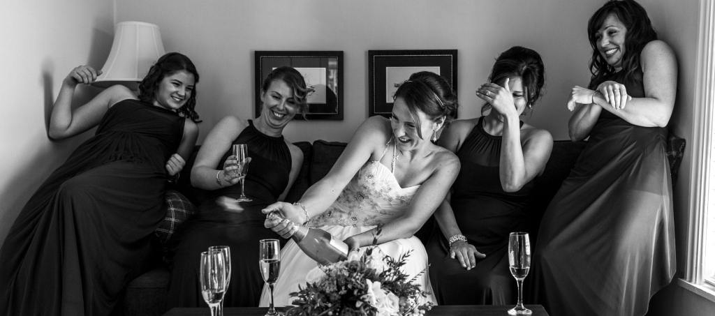 bride popping champagne during 1000 islands wedding
