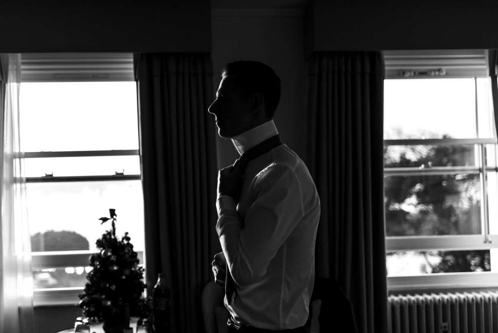 groom ties tie in dramatic window light during groom prep at Christchurch Habour Hotel & Spa