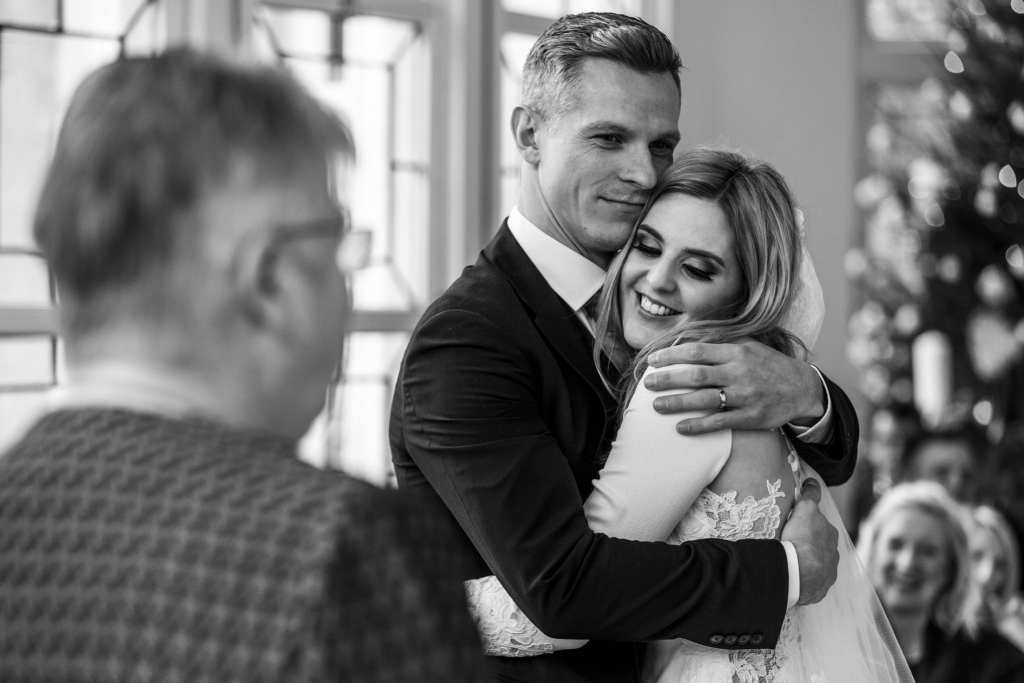 groom hugs bride after first kiss during chic New Forest wedding ceremony at Highcliffe Castle