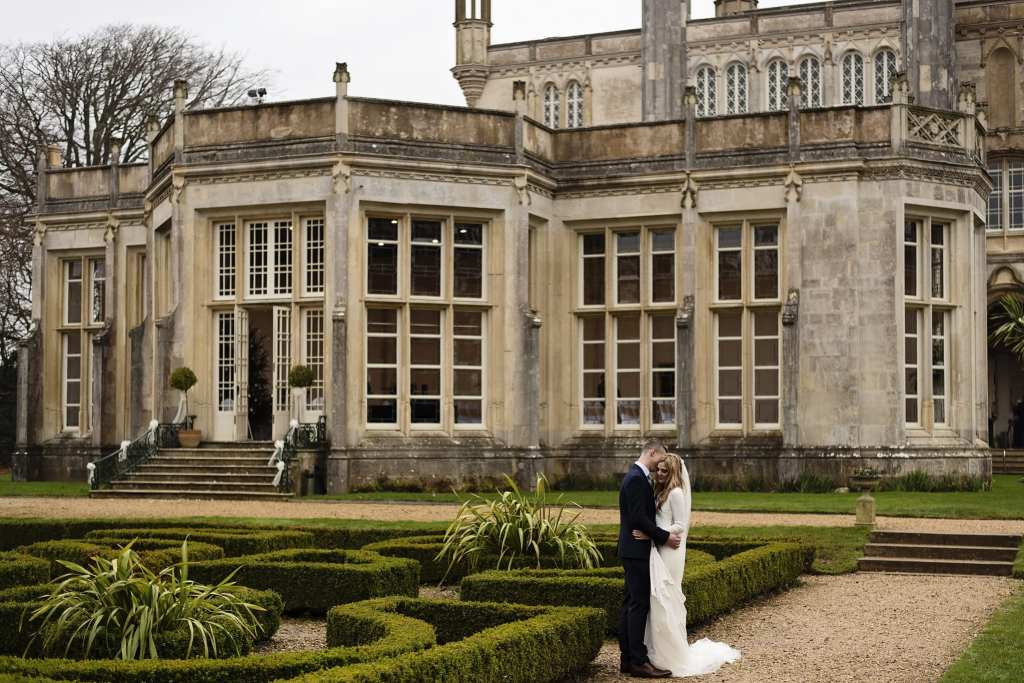groom embraces bride on pathway after chic New Forest wedding ceremony at Highcliffe Castle
