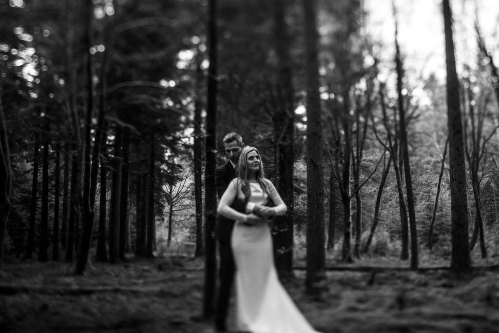 bride stands in front of groom while he wraps arms around her amongst trees on Rhinefield Ornamental Drive during New Forest wedding portraits