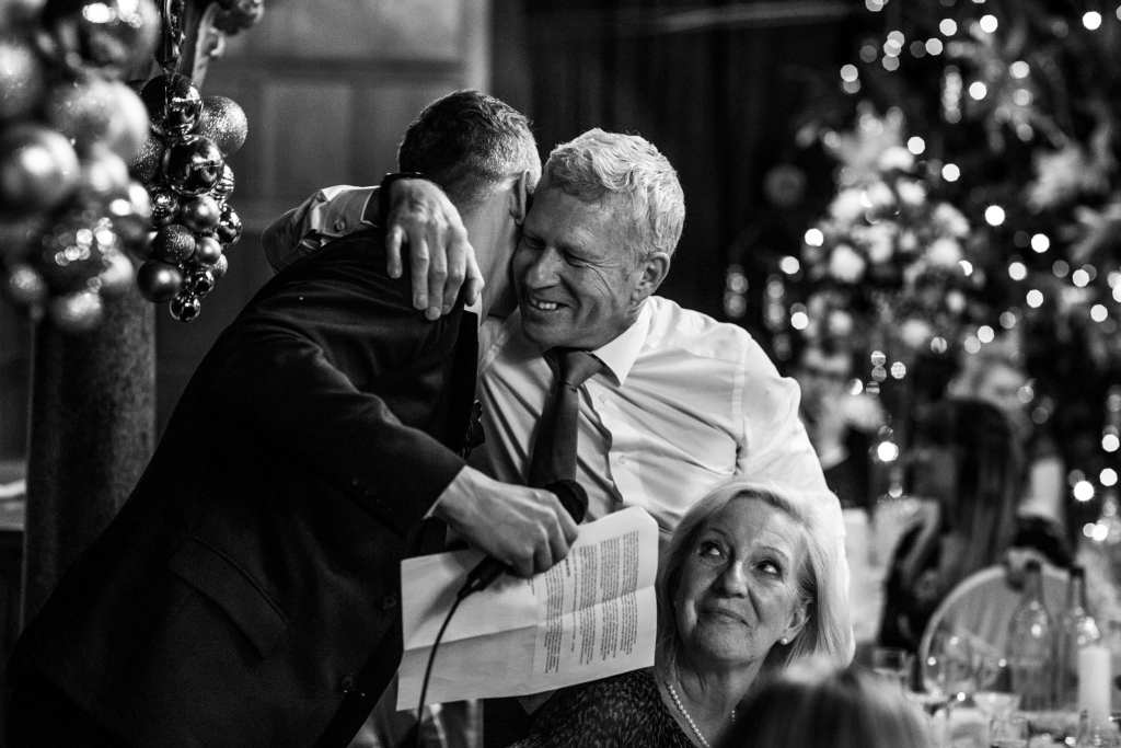 groom hugs father of the bride after speech during wedding reception at Rhinefield House