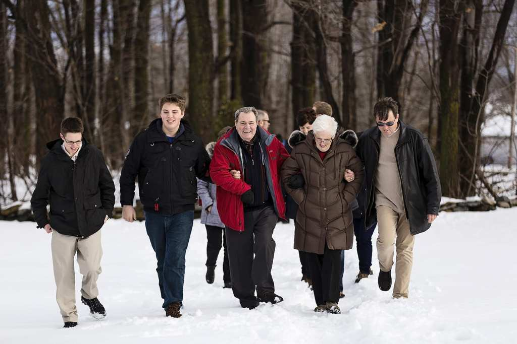 son and grandsons walk with grandparents in the snow