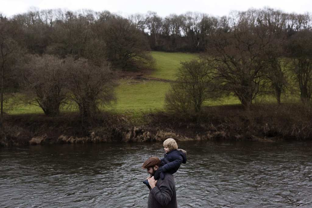 father with flatcap walks with son on shoulders framed in river during documentary session with ontario family photographer