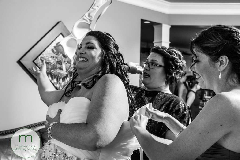 bride tosses bra behind her while bridesmaids help her with her dress
