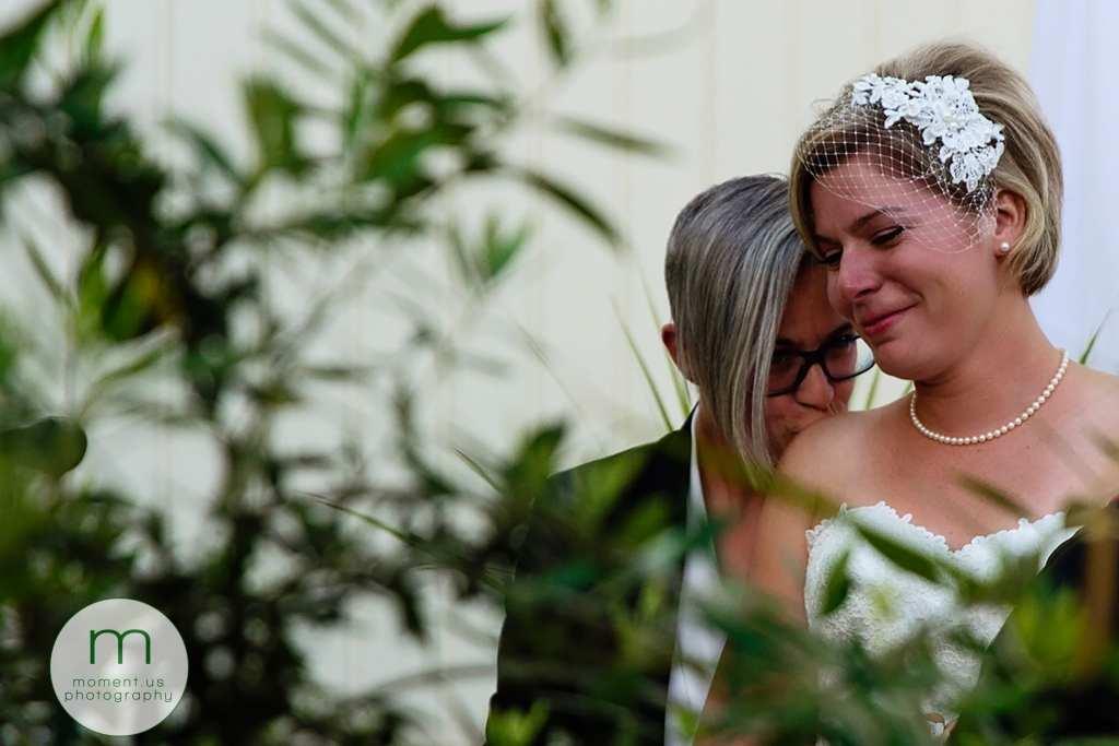bride kisses wife's shoulder during lesbian wedding ceremony