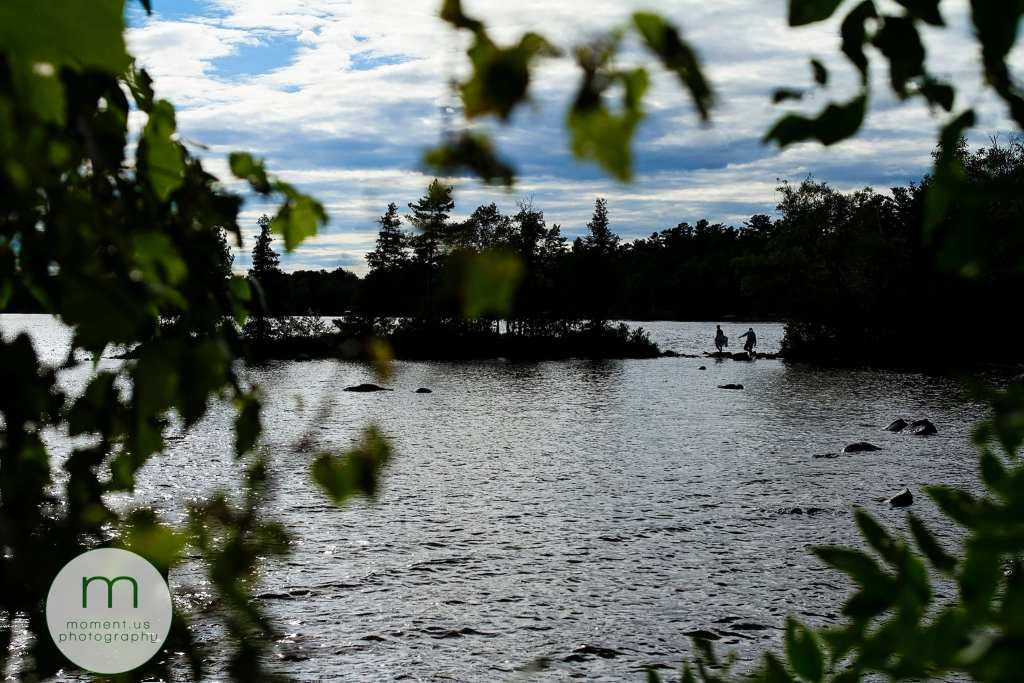 bride and groom walk on rocks into Lake Calabogie for Ontario & Quebec Wedding Photography portraits