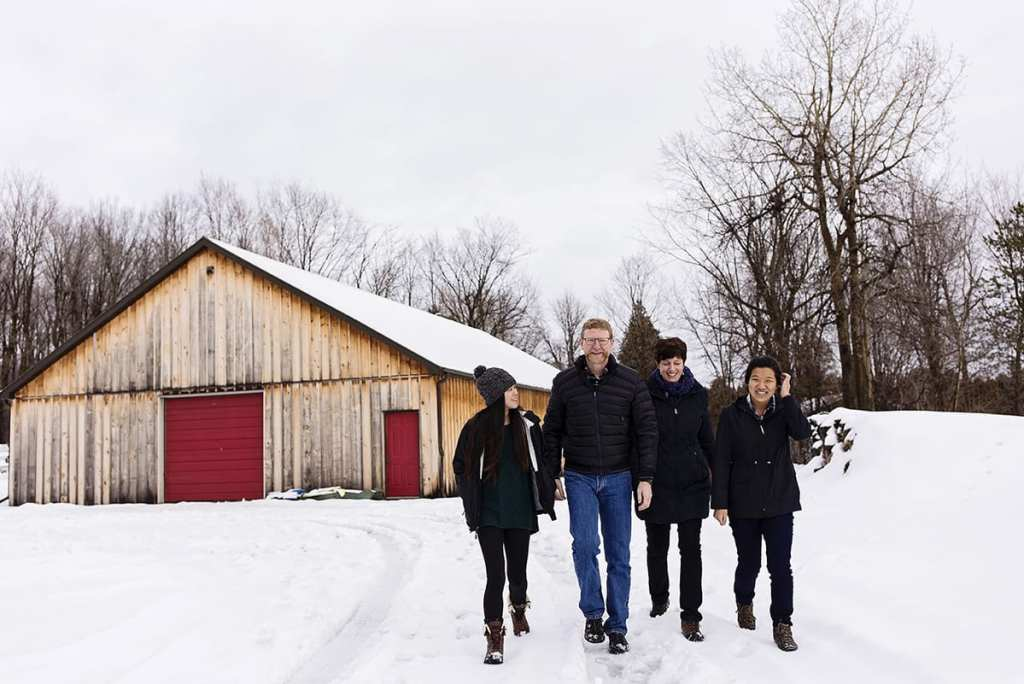 family with two daughters walks together in snow away from wood shed