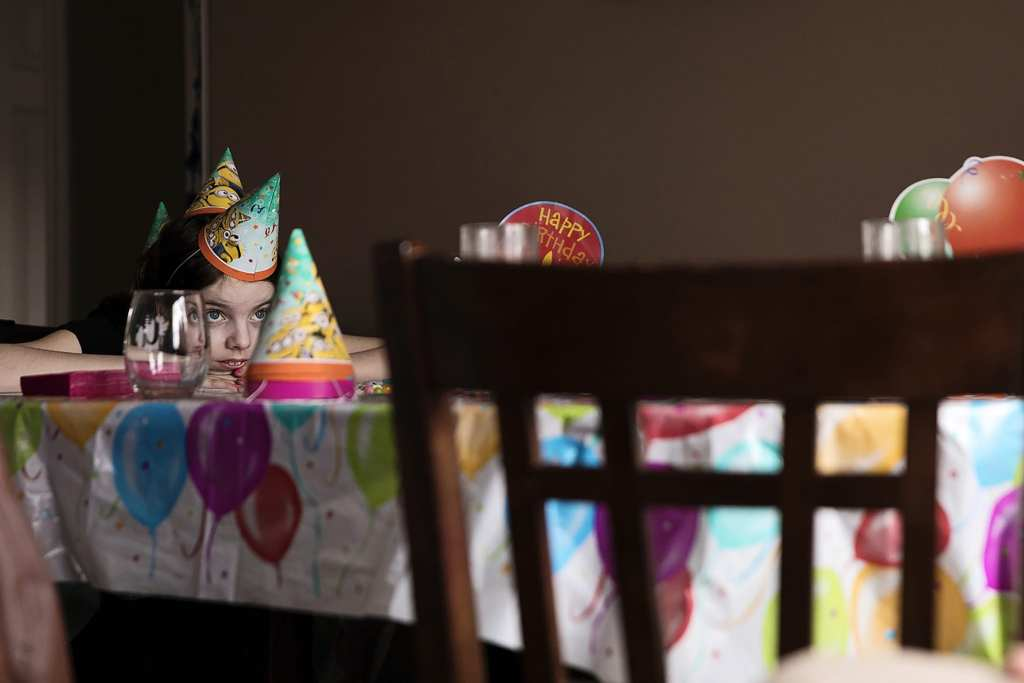 girl rests head on table while wearing three party hats like a stegosaurus