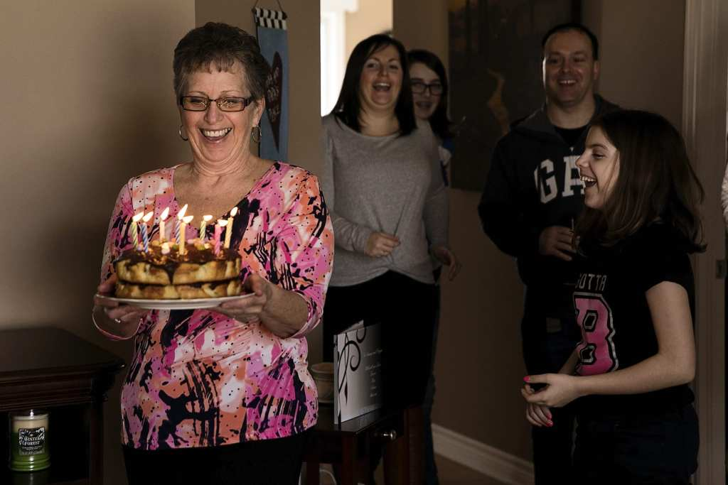 mother carries cake lit with candles while grinning widely during Eastern Ontario family photojournalism session