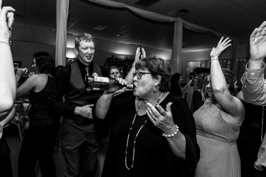 woman dancing while drinking from bottle of wine during wedding reception