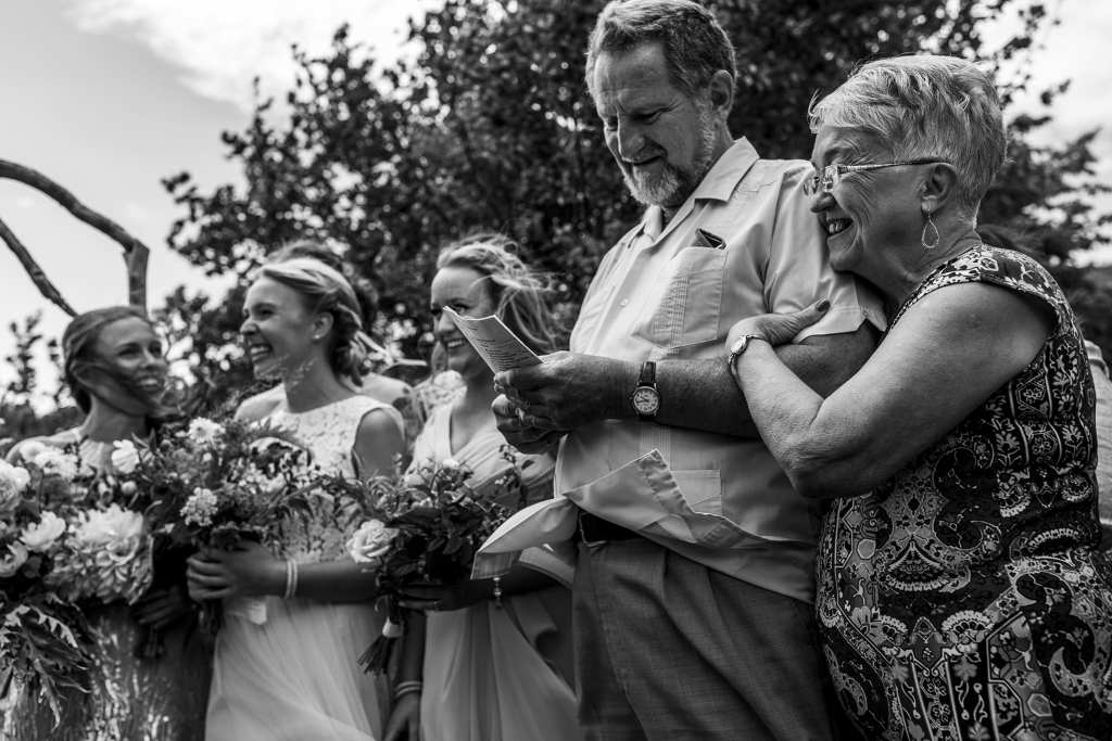 Officiant cuddles up to husband during waterfront Point Petre wedding ceremony