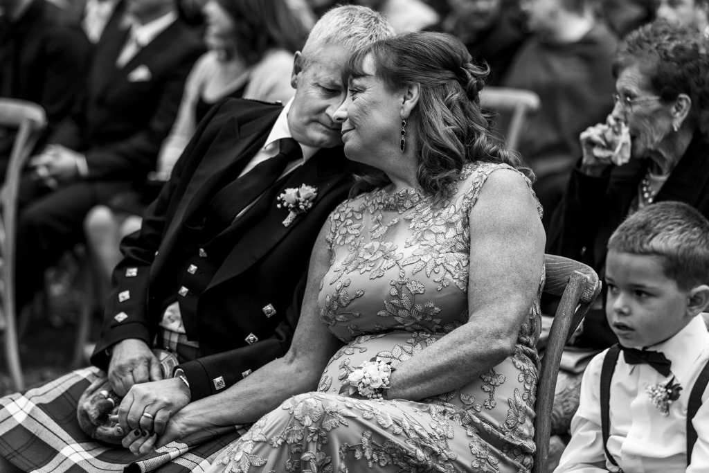 Mother and father of the bride lean heads together during Maxville Fairgrounds wedding ceremony