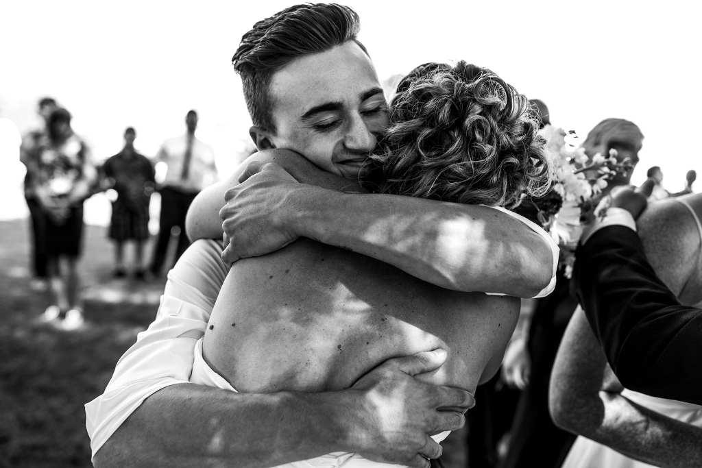 stepson hugs bride tightly