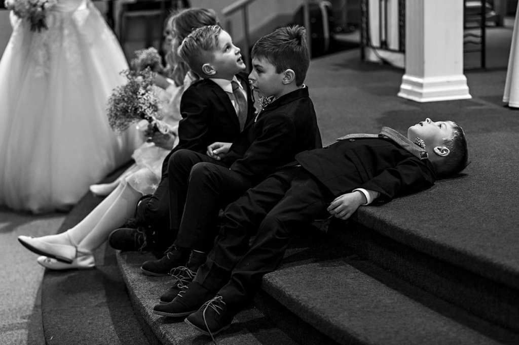 child lies on sanctuary steps after wedding ceremony in Ontario wedding photography image