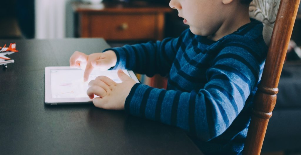 young boy interacting with online learning on a tablet