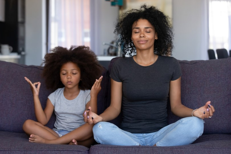 Woman finding out the benefits of yoga for moms by doing it with her daughter.