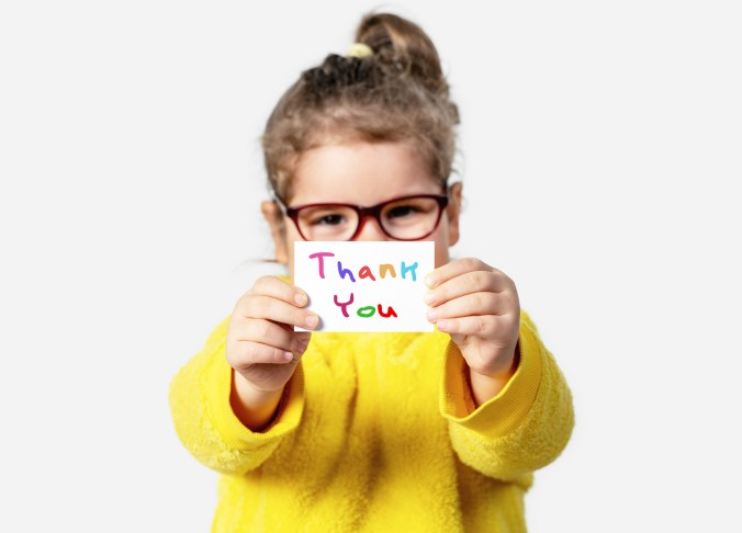 a grateful kid holding a thank you note
