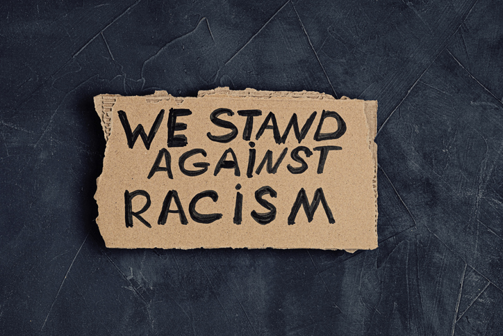 We stand against racism text on cardboard over dark background