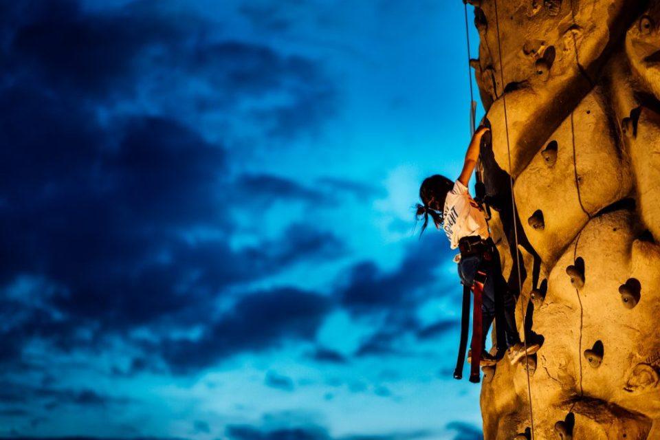 little girl climbing rock wall at River RAnch