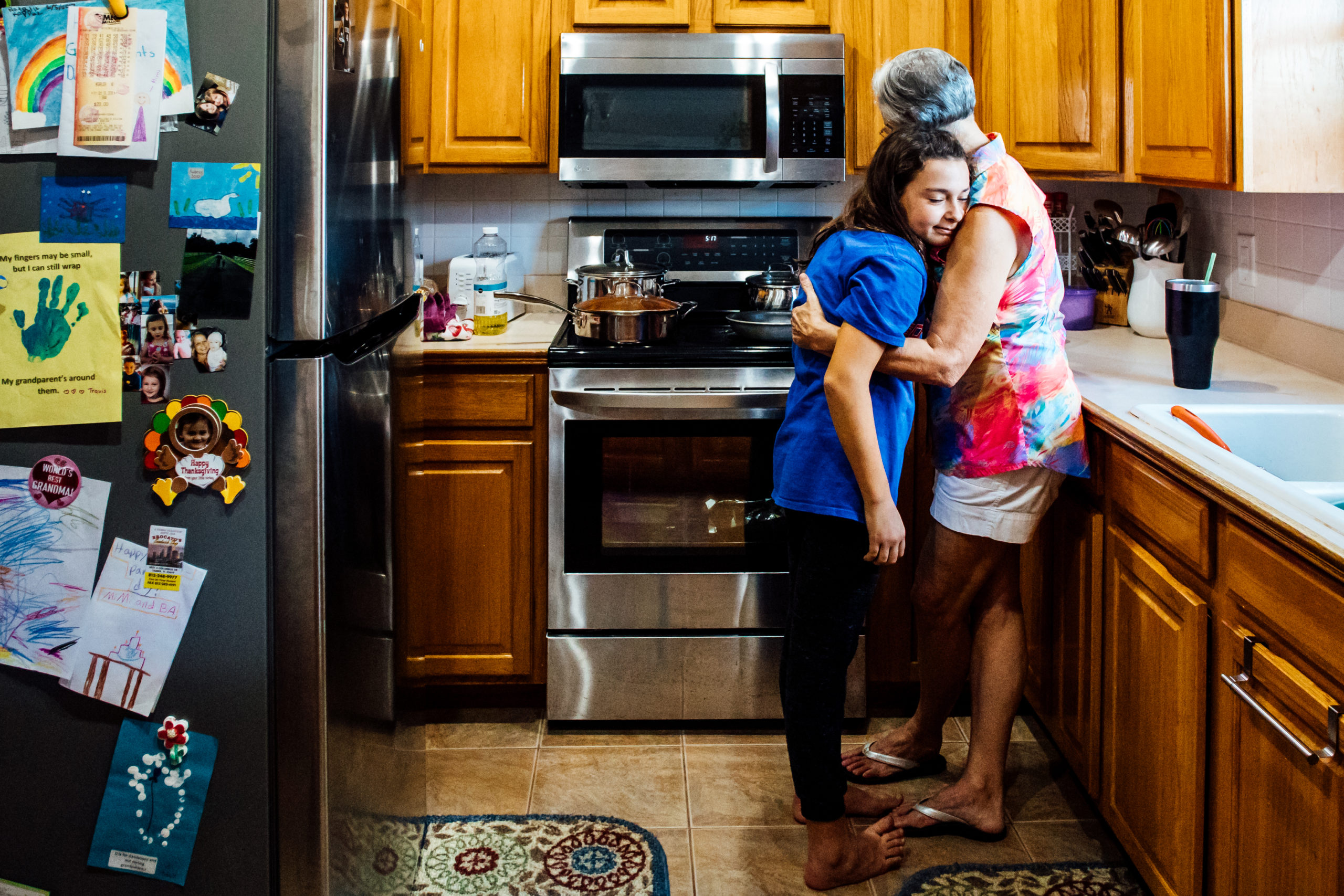 Grandmother and Granddaughter hugging in kitchen