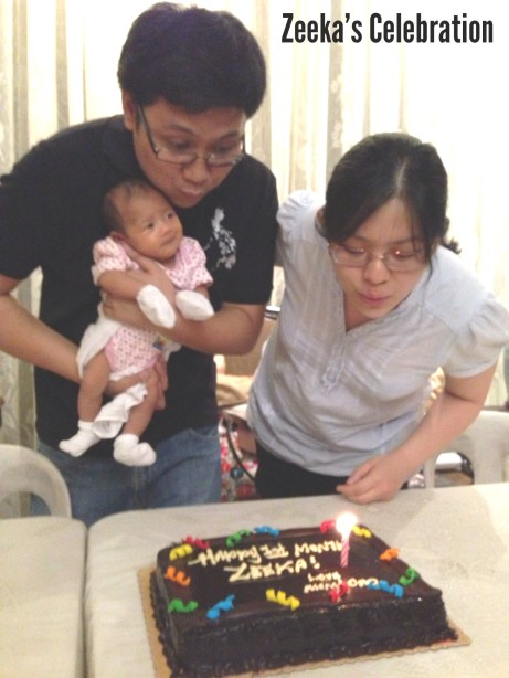 Zeeka blowing her candle with mommy and daddy!