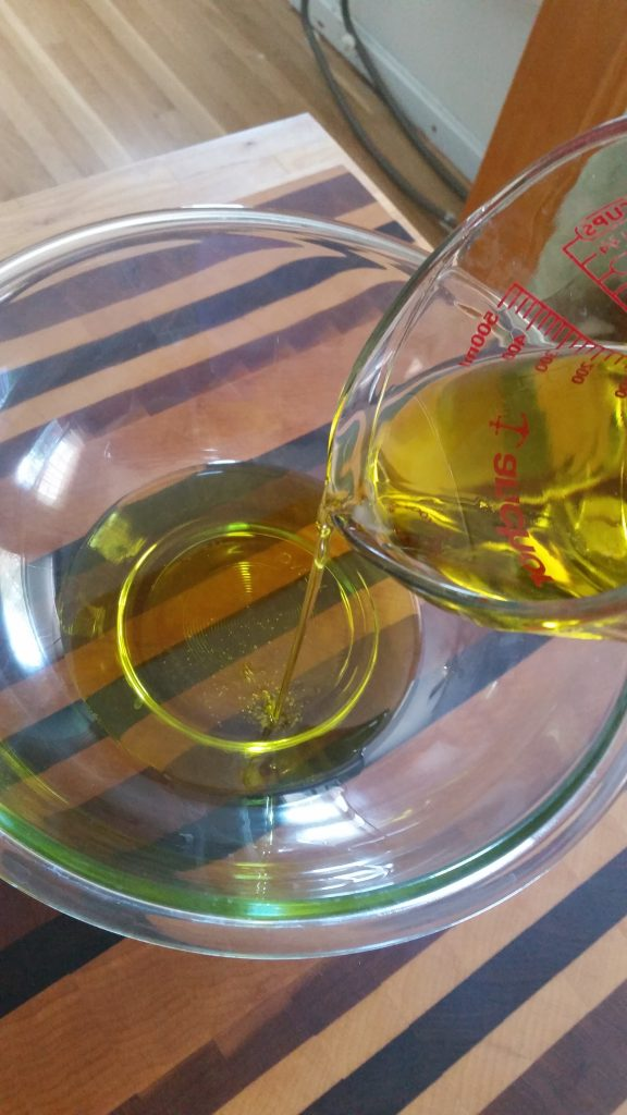 Pouring the olive oil for step 1 of the Italian Bread Salad recipe.