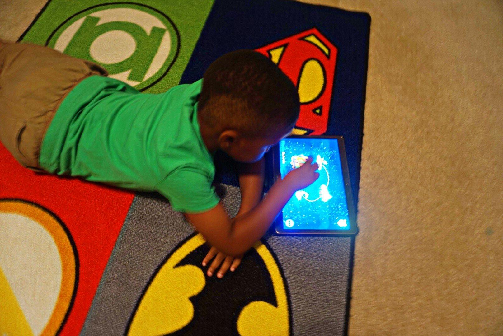 Child lying down enjoying reading app