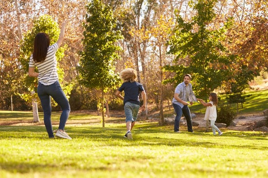 Family Playing With Frisbee In Park Together
