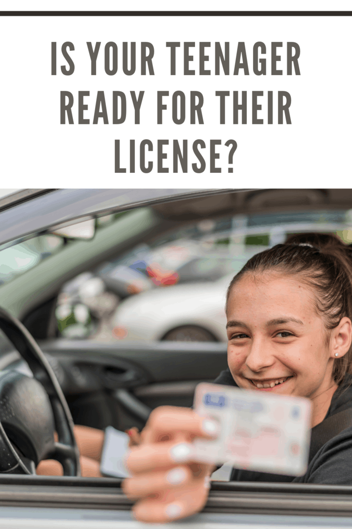 Caucasian Female teen sitting behind wheel and holding out his driving license through car window - new is our teenager ready for their license concept