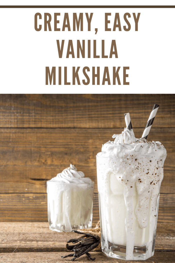 vanilla milkshakes overflowing edge of glass sprinkled with chocolate with straw. Wooden background